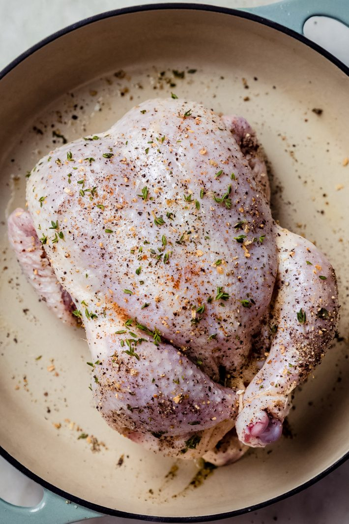 whole raw chicken with seasonings in cast iron pan
