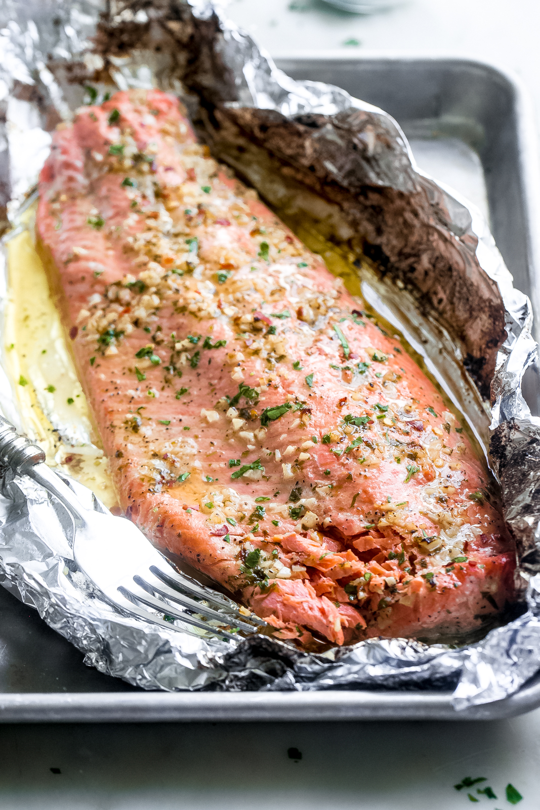 salmon filet prepared in foil with lemon garlic butter sauce drizzled on top