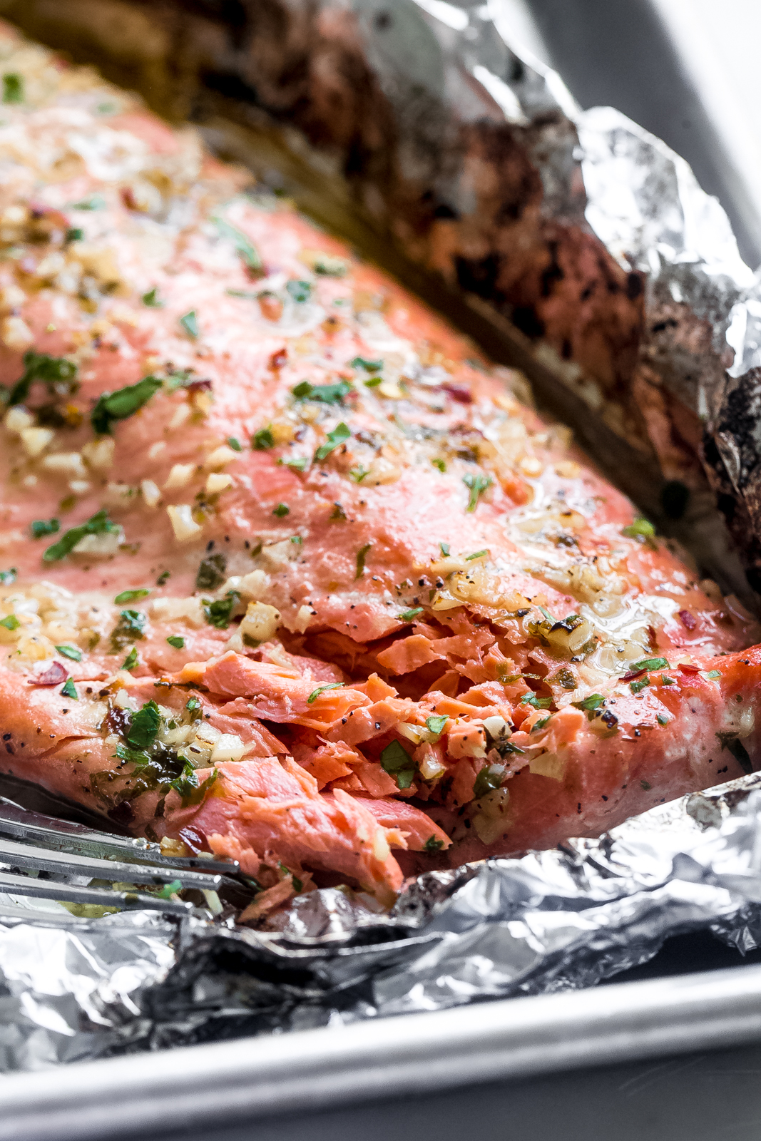 garlic butter baked salmon in foil flaked with a fork to show texture