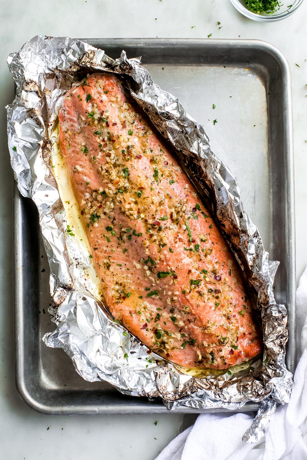 salmon filet prepared in foil on baking sheet pan