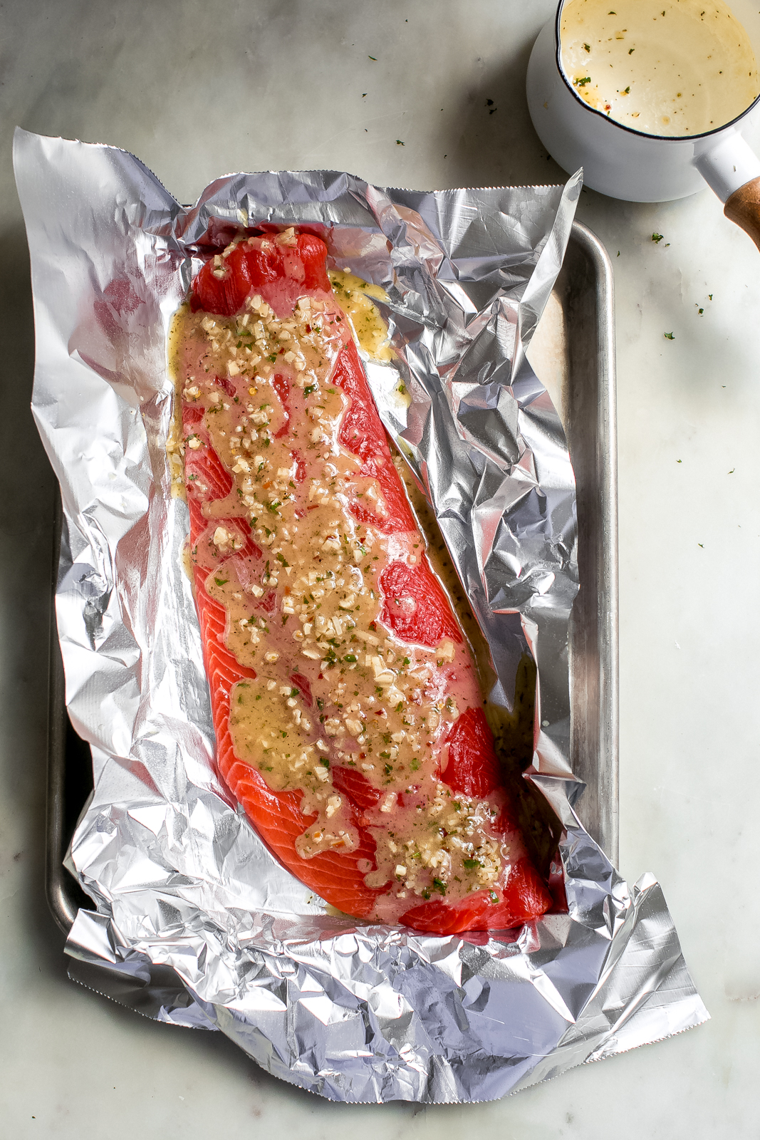 raw salmon filet on foil dressed with lemon garlic butter sauce