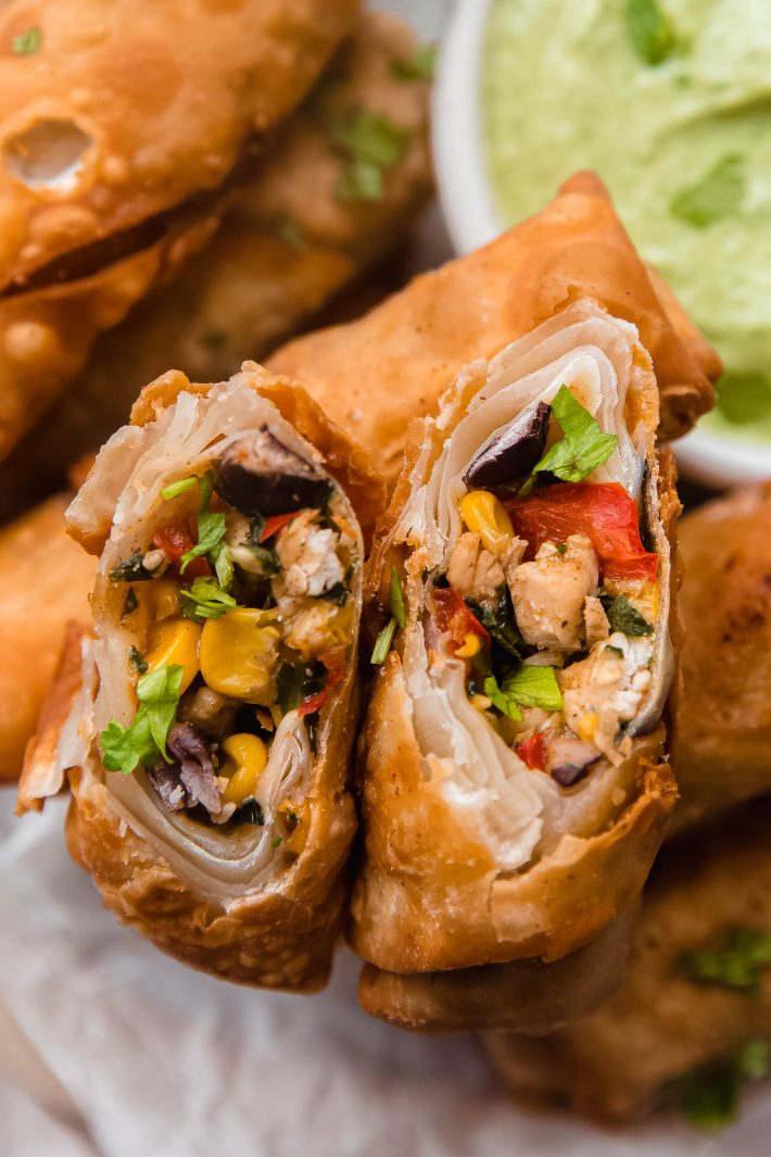 close up of cut egg roll showing corn, chicken, cilantro, beans, and bell peppers