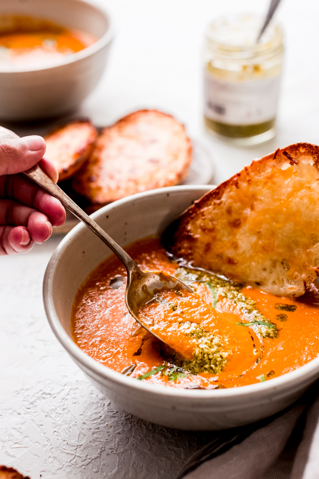 bowl of tomato basil soup with spoon being lifted by hand
