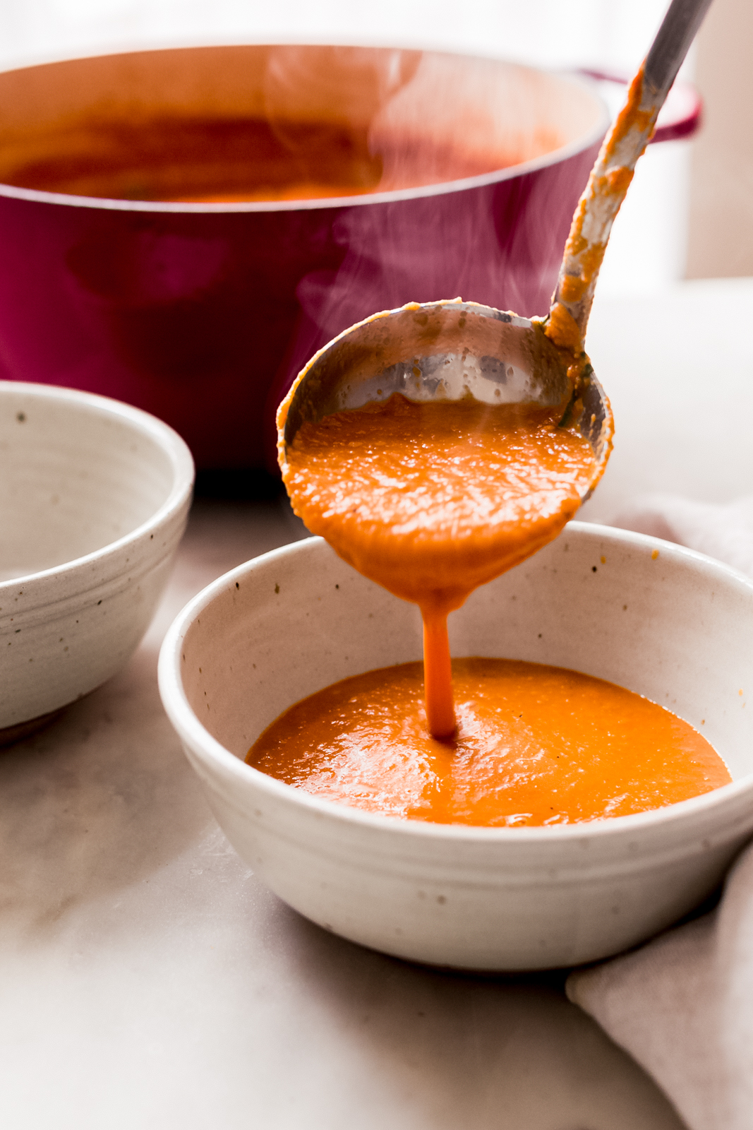 pouring a ladleful of roasted tomato soup into a bowl