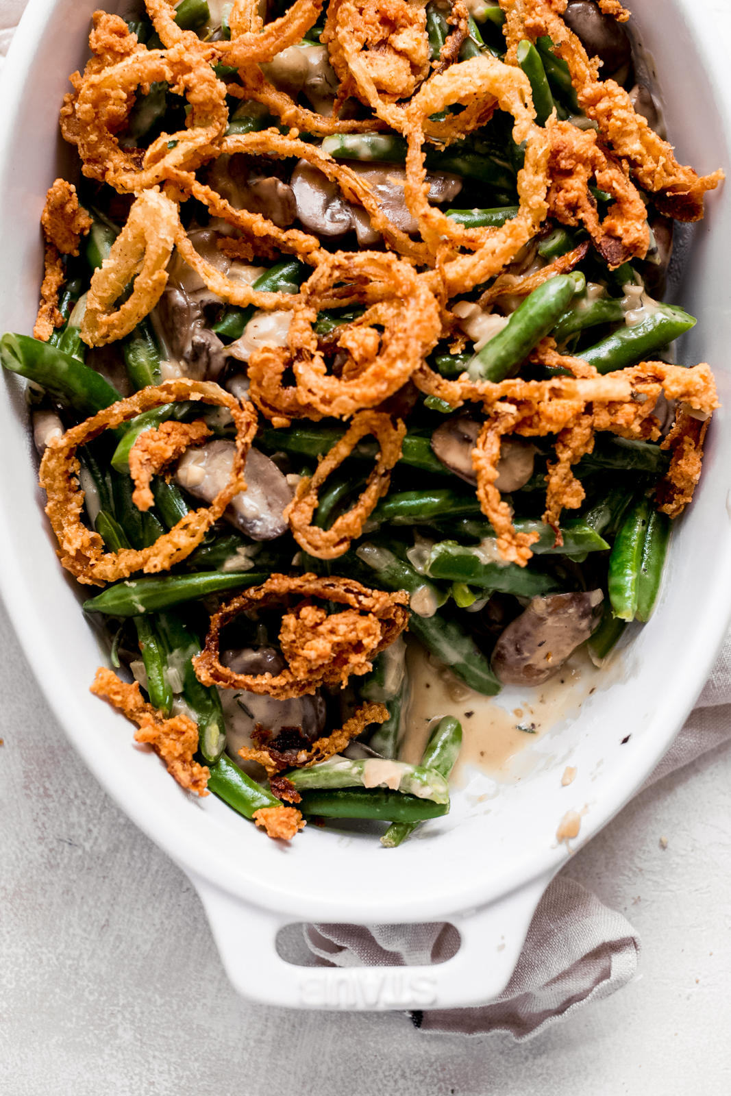 white dish with prepared green bean casserole topped with homemade fried onion rings