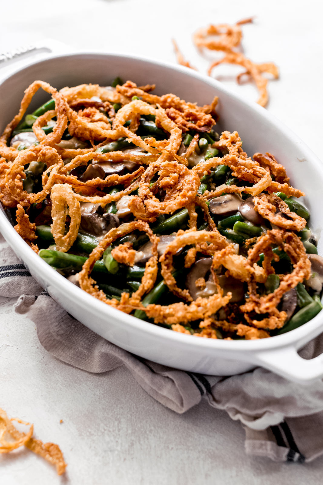 freshly made dish of green bean casserole on grey surface topped with fried onions on tea towel