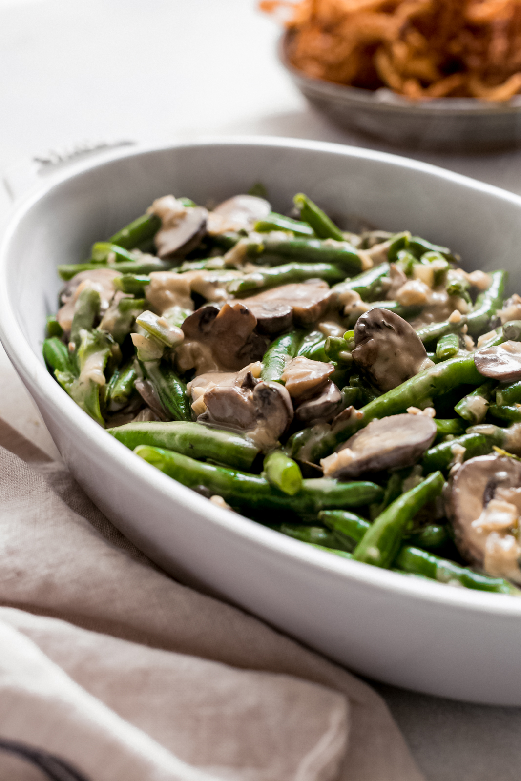 oval dish with steamed green beans topped with homemade cream of mushroom soup mix