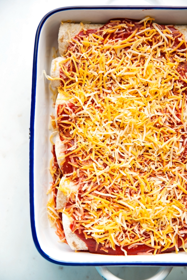 Breakfast enchiladas loaded with shredded potatoes, scrambled eggs, and black beans drizzled with my homemade ranchero sauce and shredded cheese -- comfort food to the max! #breakfast #breakfastenchiladas #enchiladas #rancherosauce | Littlespicejar.com
