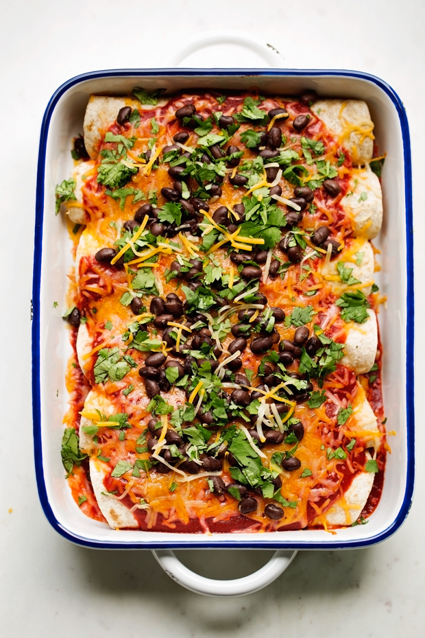 Breakfast enchiladas loaded with shredded potatoes, scrambled eggs, and black beans drizzled with my homemade ranchero sauce and shredded cheese -- comfort food to the max! #breakfast #breakfastenchiladas #enchiladas #rancherosauce   Littlespicejar.com