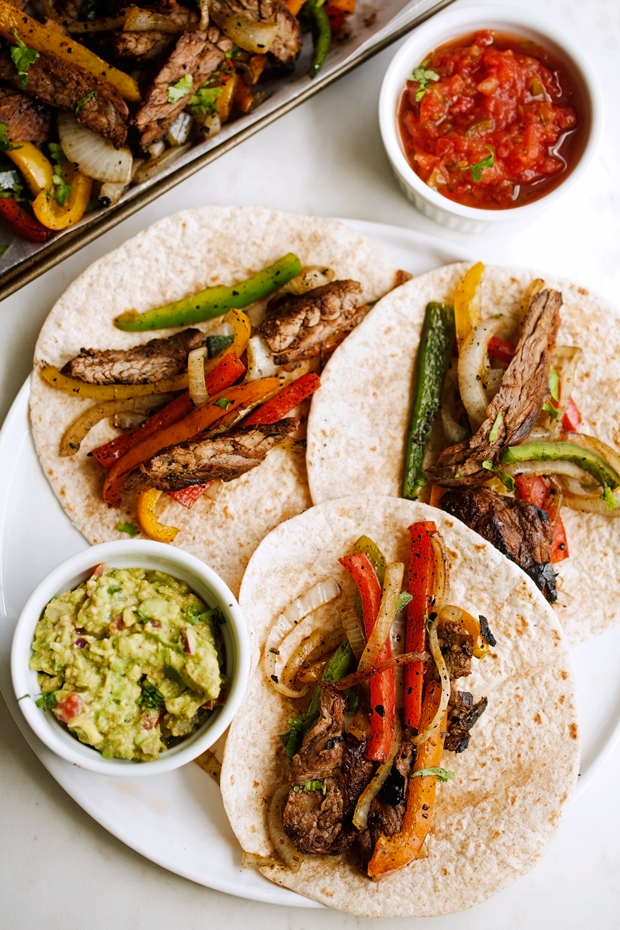 beef fajitas with peppers and onions on tortillas with bowls of guacamole and salsa