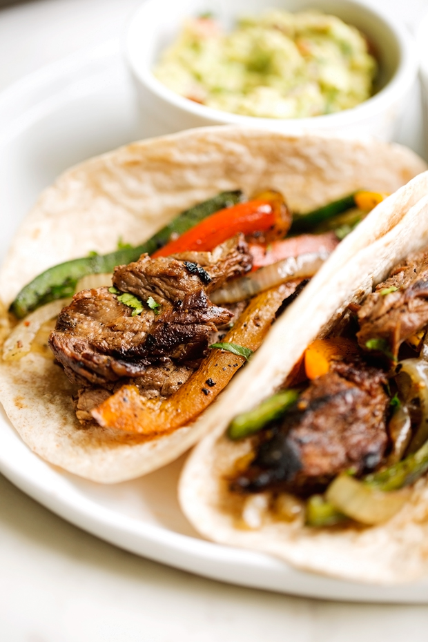 thinly sliced steak fajitas with colored peppers and onions on tortillas
