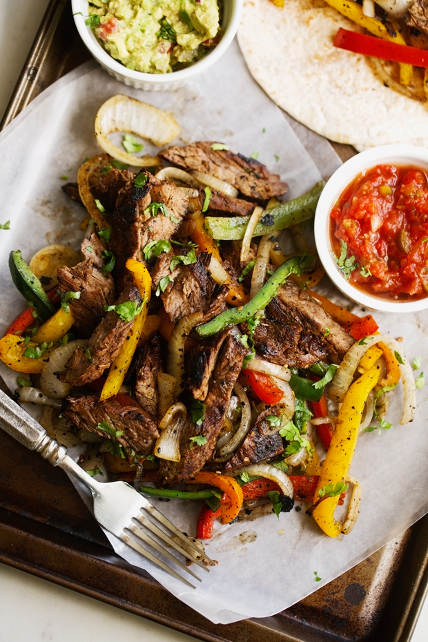thinly sliced steak fajitas with colorful peppers and onions on sheet pan