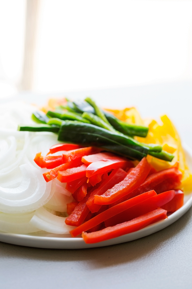 thinly sliced peppers and onions on a white plate