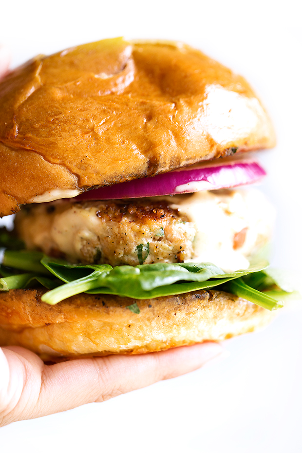 Salmon Burgers with Cajun Remoulade Sauce - A simple salmon burger that tastes gourmet! Topped with homemade remoulade sauce! #salmonburger #remouladesauce #salmoncakes #salmonpatties | Littlespicejar.com