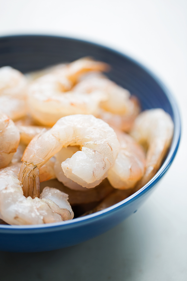 cleaned shrimp in a blue bowl on white marble