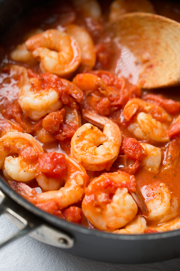 spicy shrimp and tomato mixture in saute pan with wooden spoon