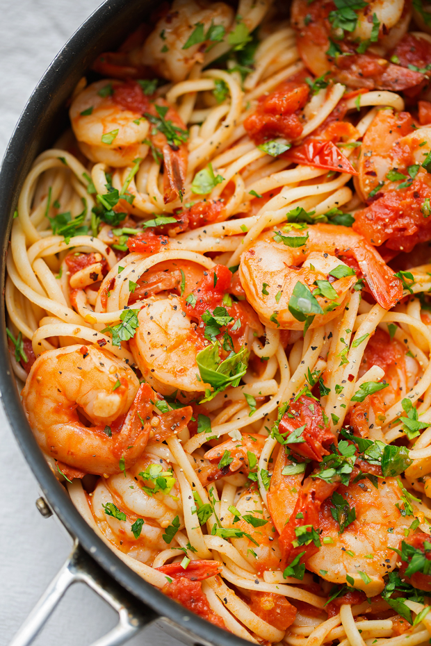spicy shrimp pasta in saute pan tipped with fresh parsley