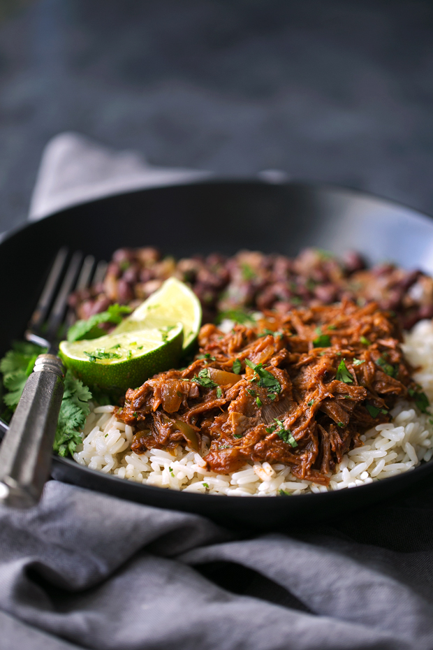 close up of plate with cilantro rice, cuban shredded beef with lime wedges and cilantro
