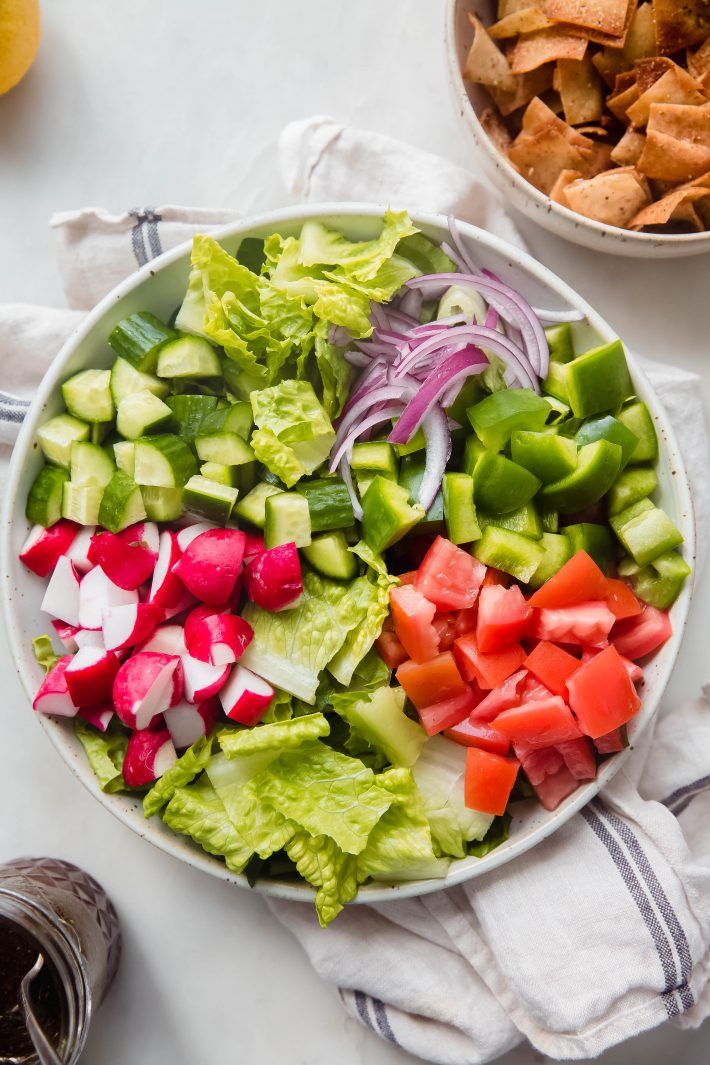 radishes, cucumbers, onions, bell peppers and tomatoes on a bed on lettuce in bowl