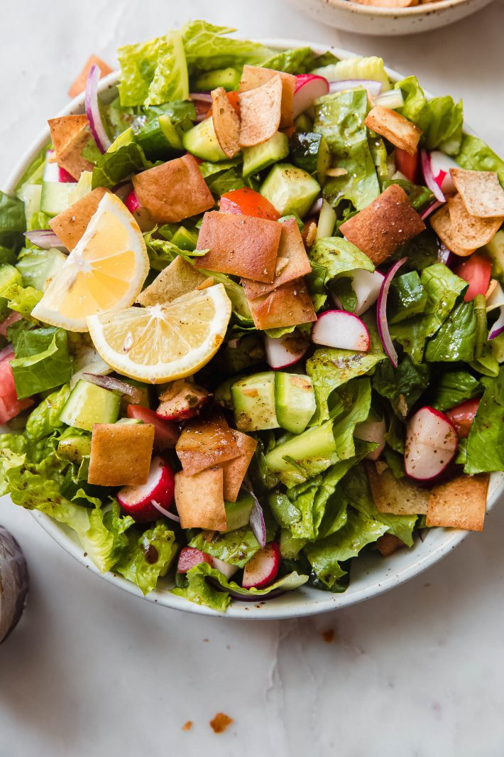 prepared fattoush salad with pita chips and dressing in speckled bowl