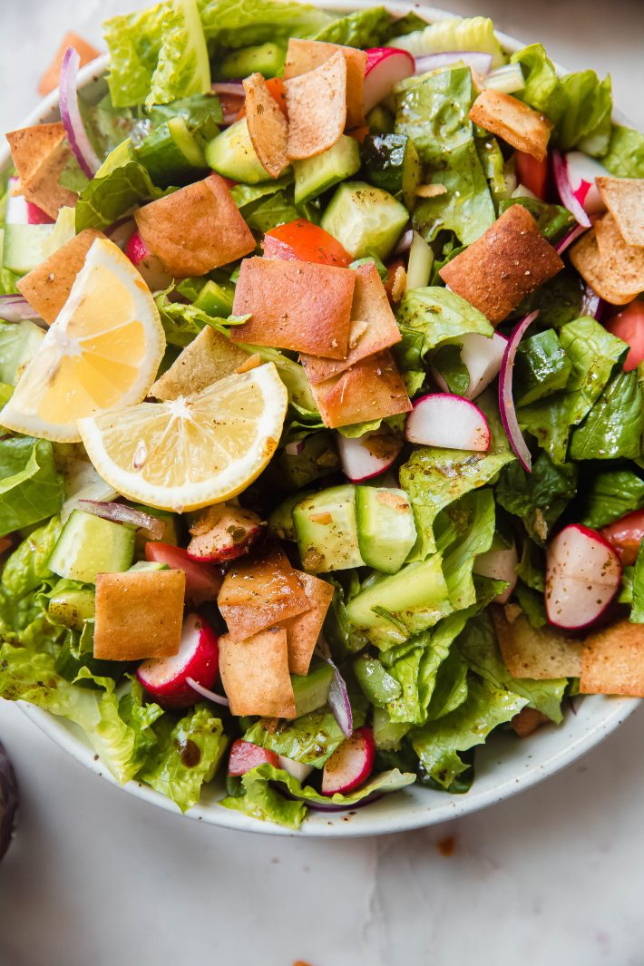 fattoush salad topped with lemon wedges in speckled bowl