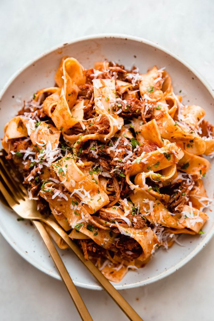 beef ragu with pappardelle pasta on a plate with fork and spoon