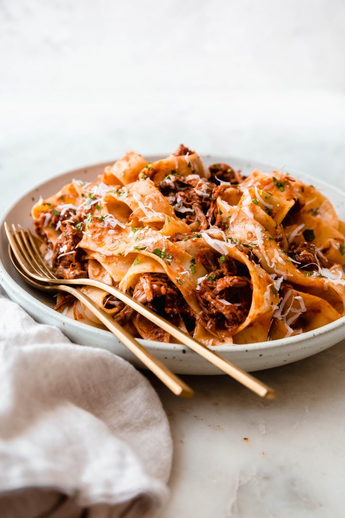 rimmed plate filled with ragu tossed with pappardelle