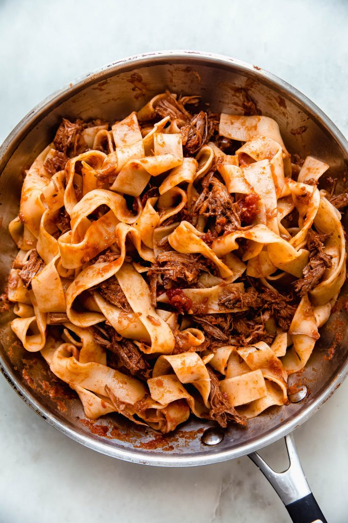 skillet with tossed ragu and pappardelle