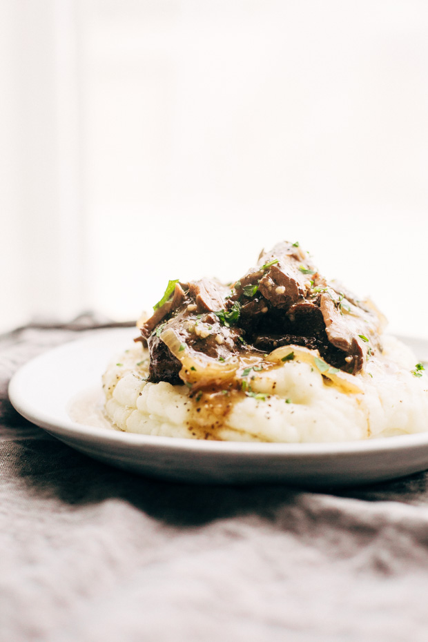 plate showing mashed potatoes topped with brown gravy and onion pot roast