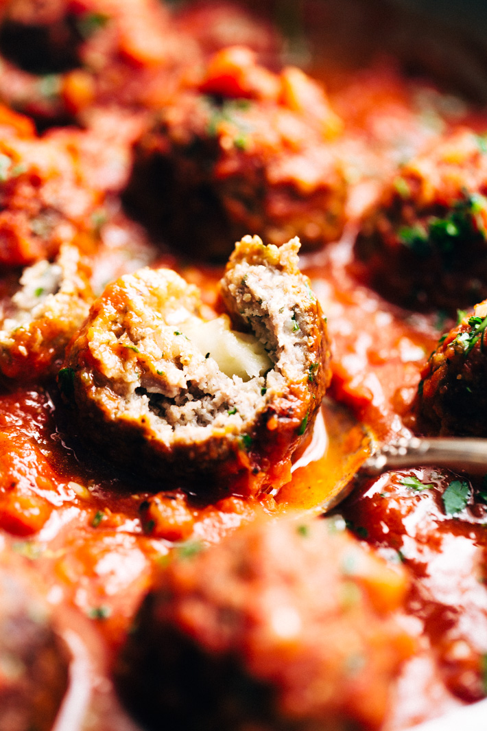 Cheesy Stuffed Meatballs in Homemade Tomato Sauce - The perfect meal for spaghetti and meatball night! Or serve them as party appetizers for New Years, Christmas, and Super Bowl parties! #stuffedmeatballs #cheesestuffedmeatballs #homemadetomatosauce | Littlespicejar.com