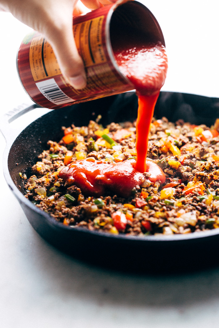 pouring tomato sauce into skillet with ground beef mixture and veggies
