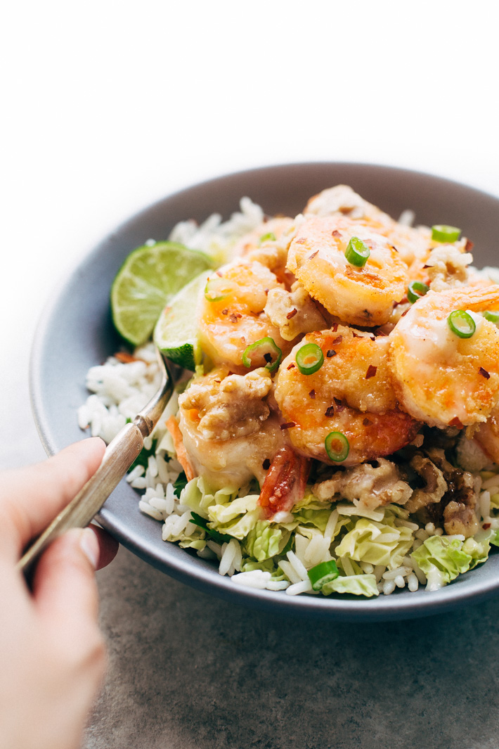 Lighter Honey Walnut Shrimp - A lighter take on the takeout classic! We're pan frying the shrimp in just a hint of oil, tossing it together with candied walnuts and a creamy sauce then serving it over a big mound of greens and rice! #honeywalnutshrimp #takeoutfakeout #walnutshrimp #shrimp   Littlespicejar.com