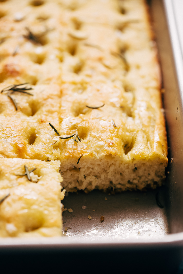 side shot of focaccia in baking pan to show inside texture