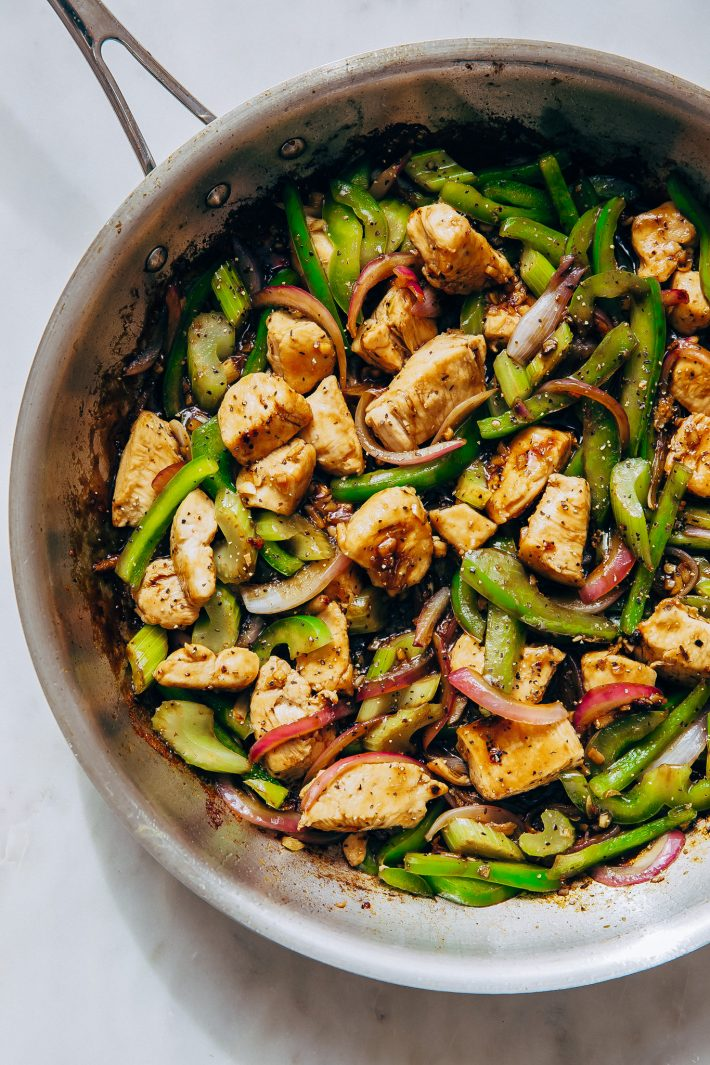 skillet with prepared pepper chicken stir fry on white marble