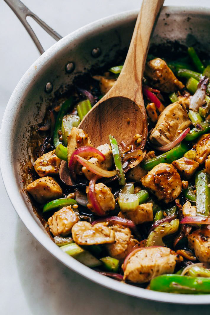 skillet with wooden spoon and prepared chicken stir fry with vegetables