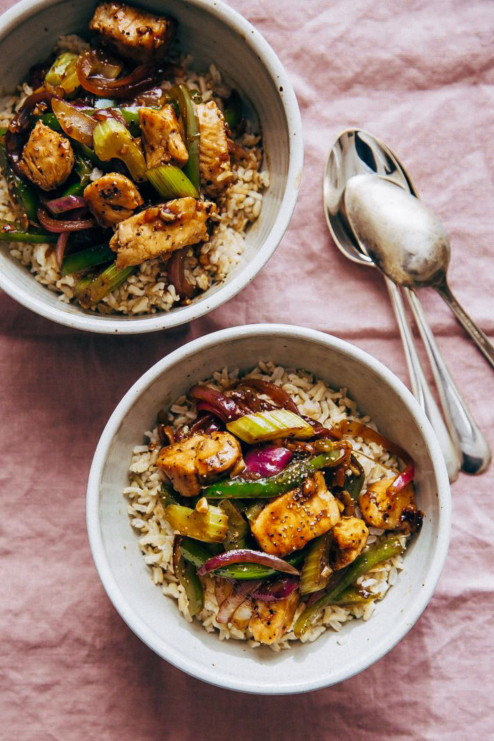 bowls of rice topped with chicken stir fry on mauve linen napkin with spoons
