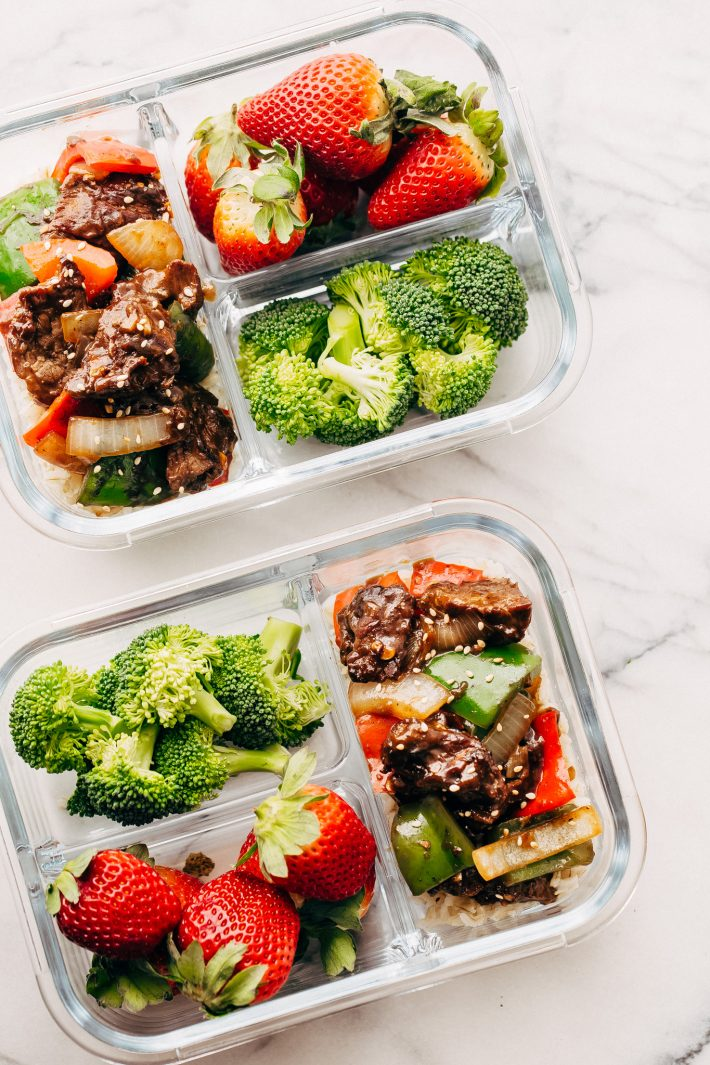 meal prep box with three divider filled with stir fry, broccoli, and strawberries
