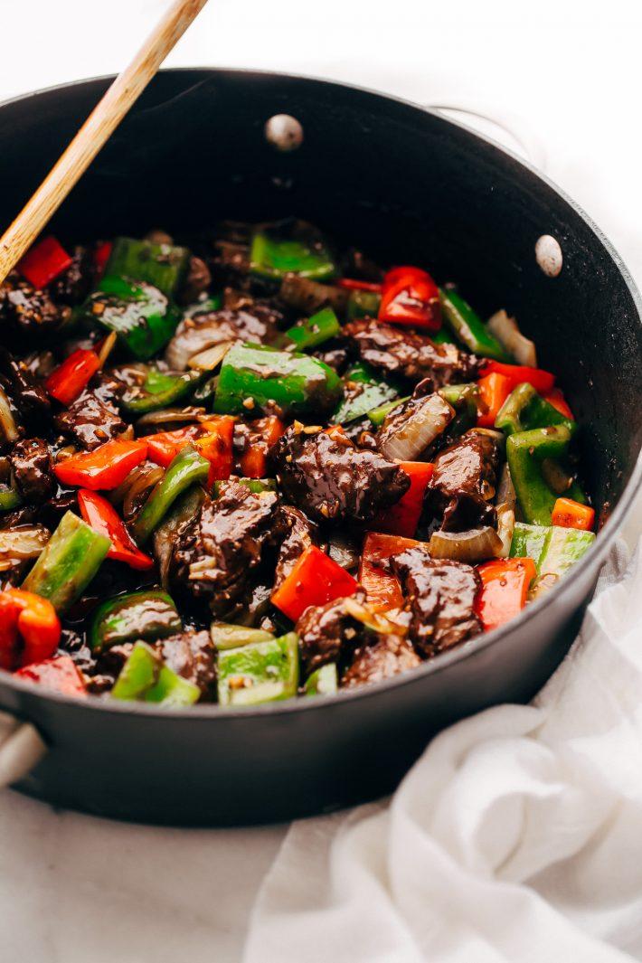 side shot of prepared pepper steak stir fry in saute pan with wooden spoon
