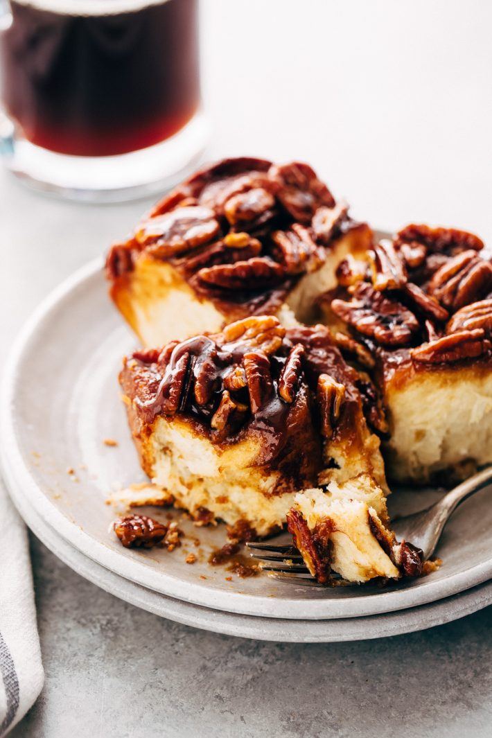 Gooey Pecan Sticky Buns - Learn how to make sticky buns at home from scratch. These sticky buns have a caramel pecan topping and swirls of cinnamon inside! #stickybuns #maplepecanstickybuns #pecanstickybuns #cinnabon #cinnamonrolls | Littlespicejar.com