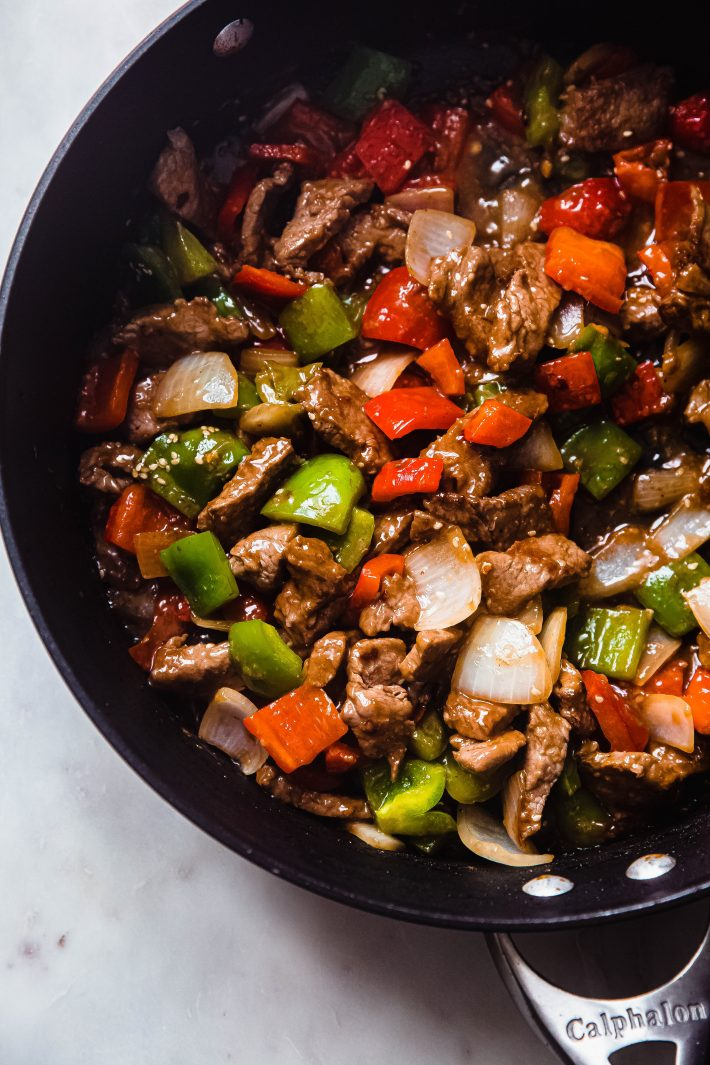 thinly sliced beef and peppers steak in pan