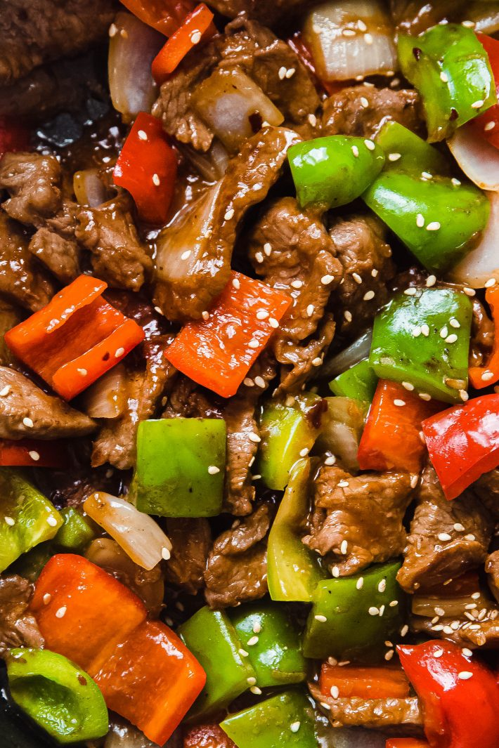 peppers and steak topped with sesame seeds in pan