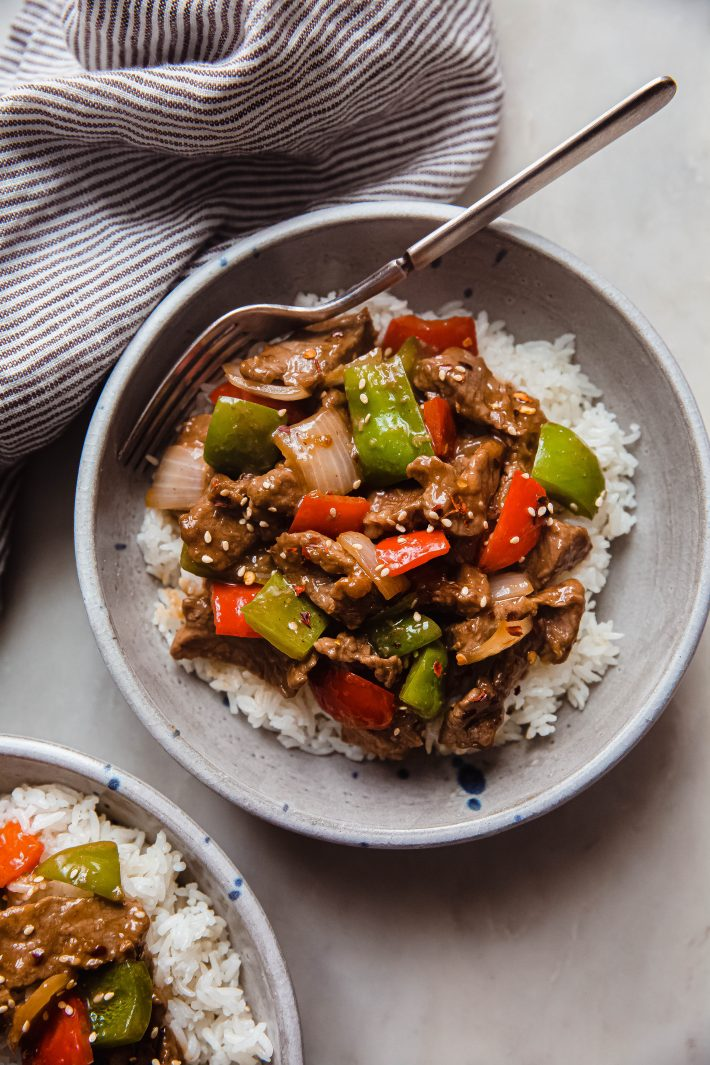 bowl of rice topped with pepper steak stir fry