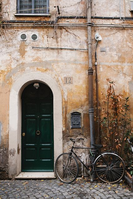 image of green door in Italy with a bike leaning against the wall
