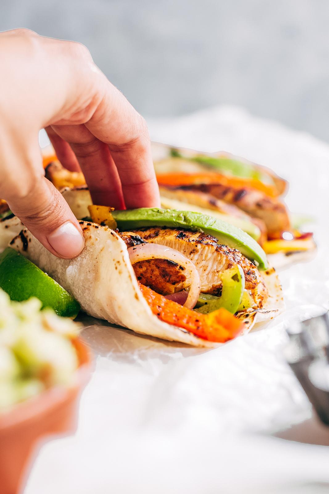 hand holding tortilla with chicken fajitas, sliced avocados and sautéed veggies