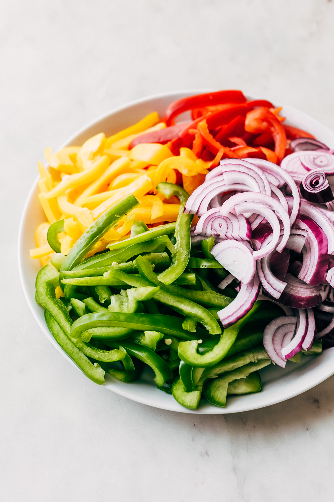 colorful sliced peppers and onions on white plate