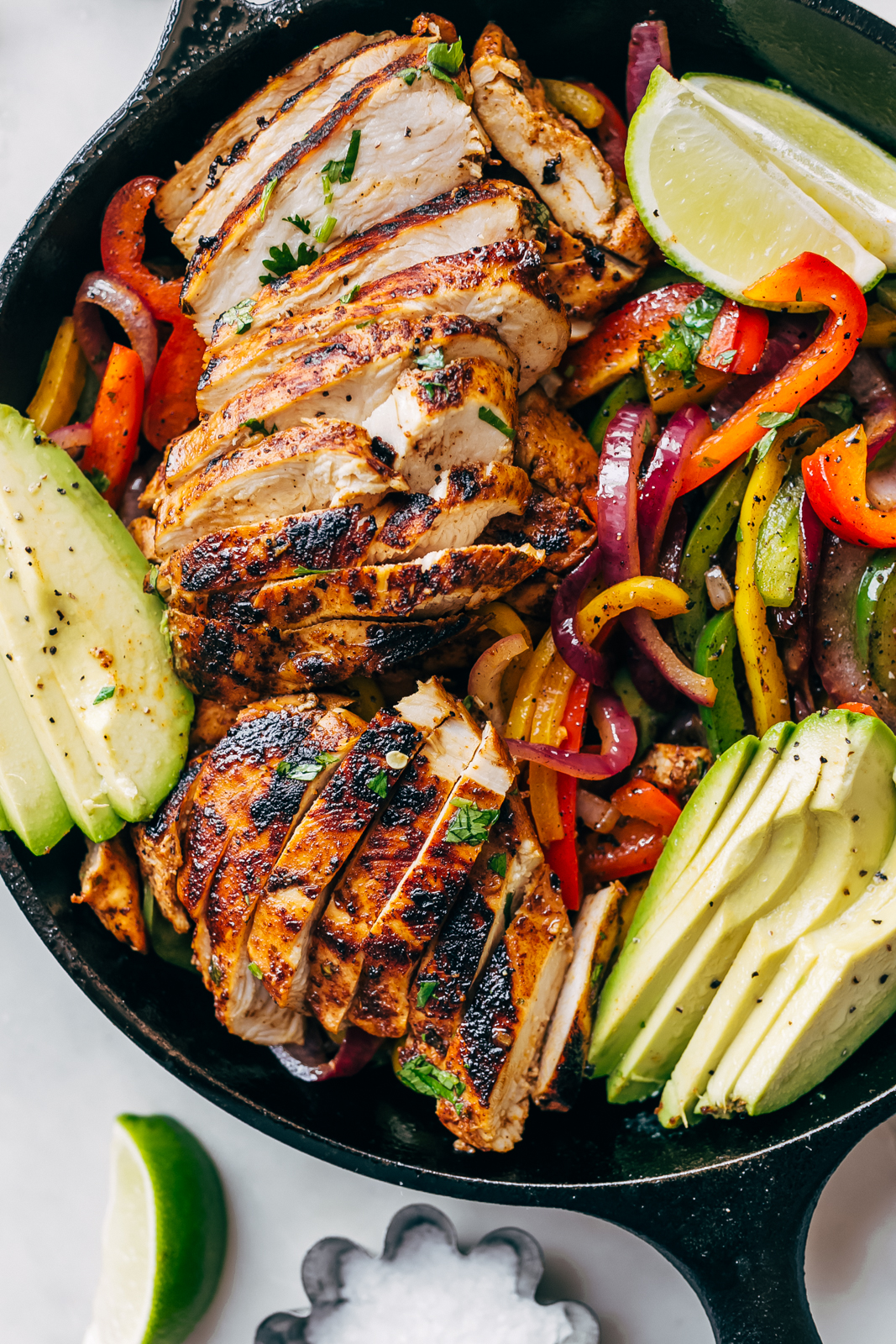 close up of sliced chicken fajitas with veggies, lime wedges, and avocado slices
