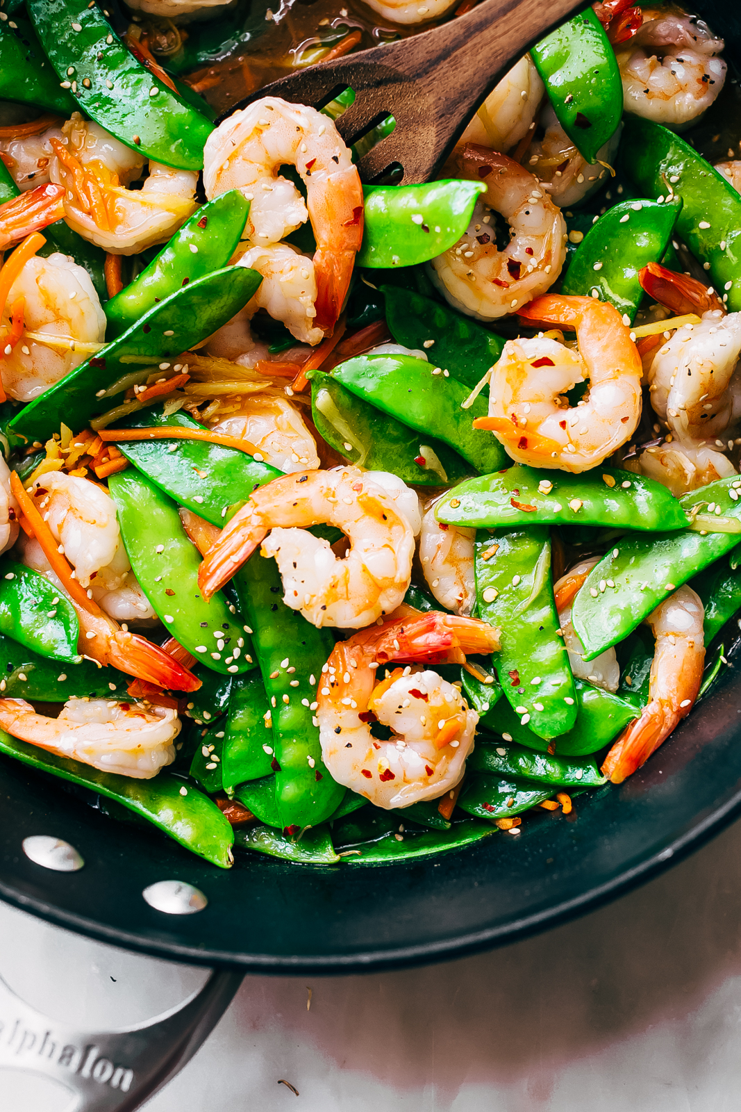 close up of shrimp stir fry showing curved shrimp and bright green snow peas