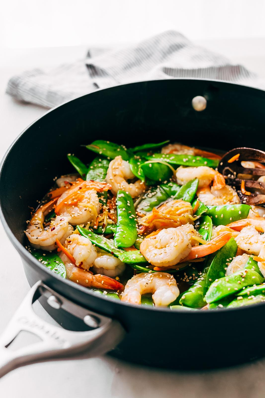 side shot of saute pan holding prepared shrimp stir fry