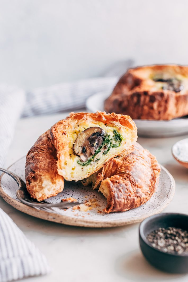 prepared croissant boats cut in half on speckled plate showing spinach and mushroom