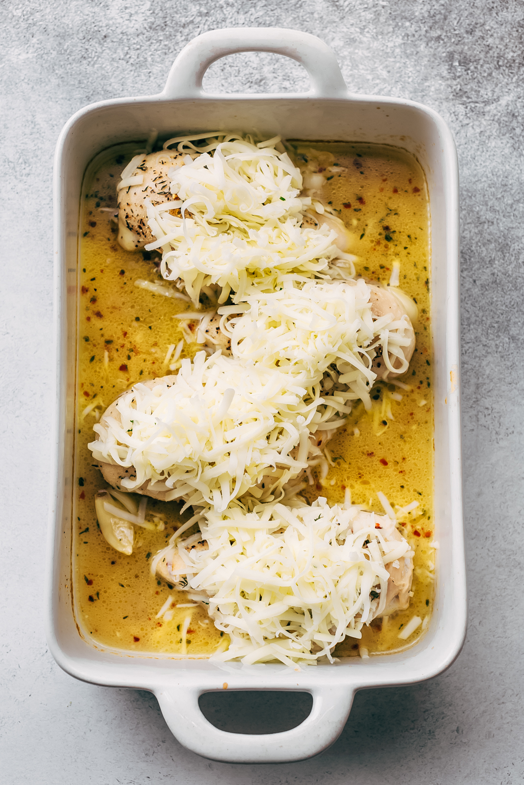 half-baked chicken topped with shredded mozzarella cheese in white baking dish
